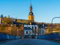Germany, Famous old church schlosskirche behind blue bridge of saarbruecken old town in warm morning light