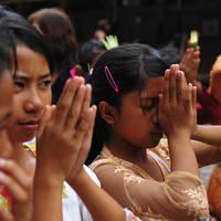 Biddende meisjes tijdens een ceremonie